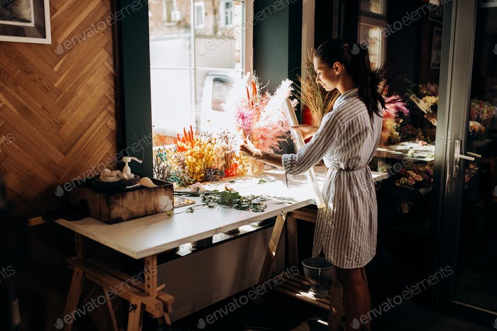 Florist dressed in a striped dress stands near the table with colorful dried flowers and holds
