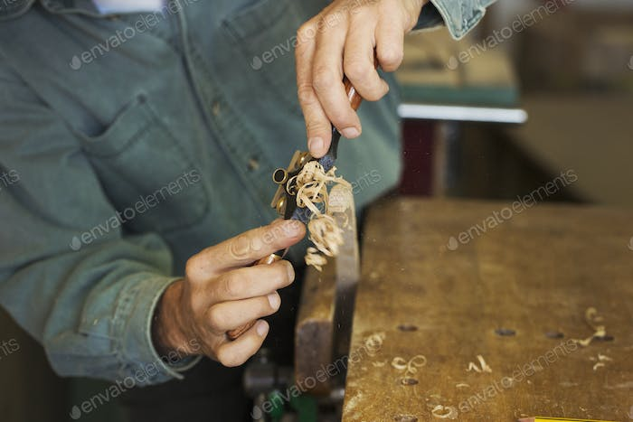 A craftsman using a spokeshave with blade to trim a piece of wood in a clamp.