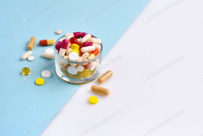 A glass full of pills, tablets, capsules on blue and white background