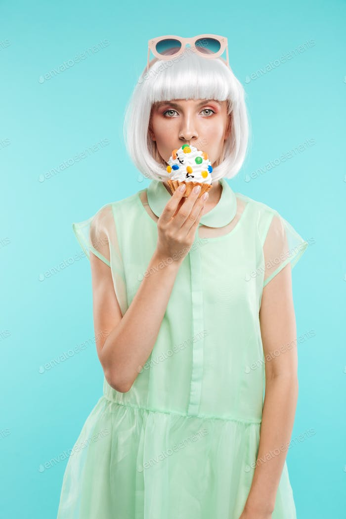 Cute blonde young woman standing and eating cupcake