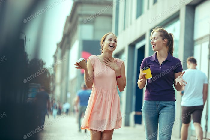 Beautiful girls holding paper coffee cup and enjoying the walk in the city