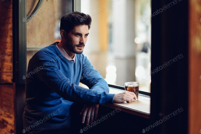 Pensive guy with modern hairstyle near a window drinking a soda