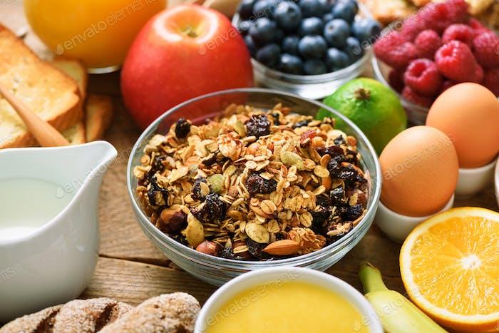 Gesunde Frühstückszutaten, Lebensmittelrahmen. Müsli, Ei, Nüsse, Früchte, Beeren, Toast, Milch, Joghurt