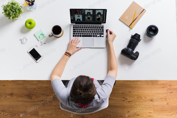 woman with camera flash drive and laptop at table