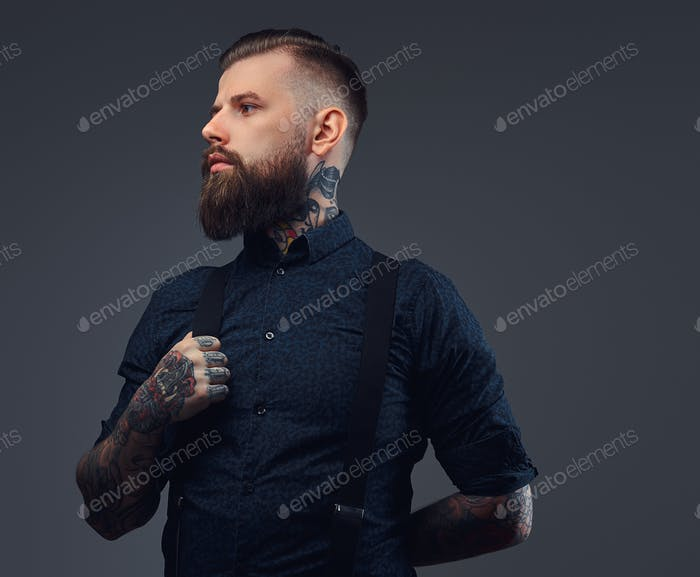 Portrait of a handsome old-fashioned hipster in a blue shirt and suspenders in a dark studio.