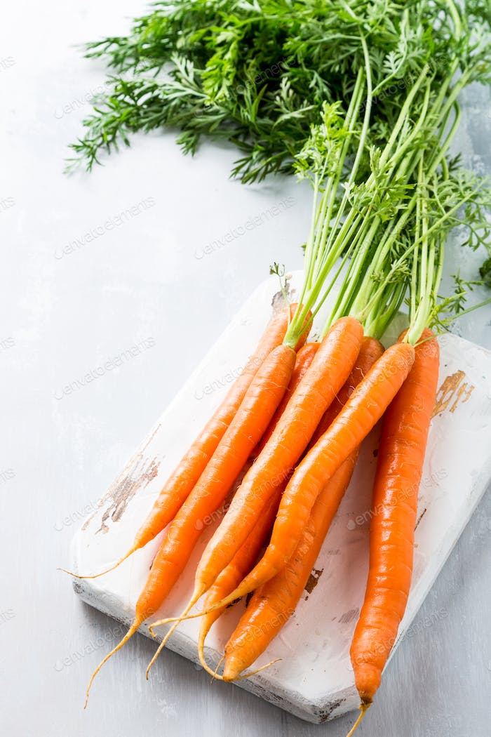 Fresh carrots on wooden board