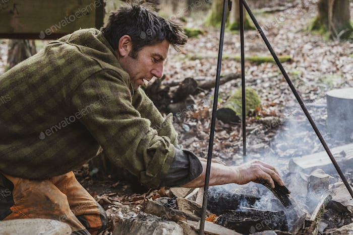 Man sitting by a camp fire in a forest.