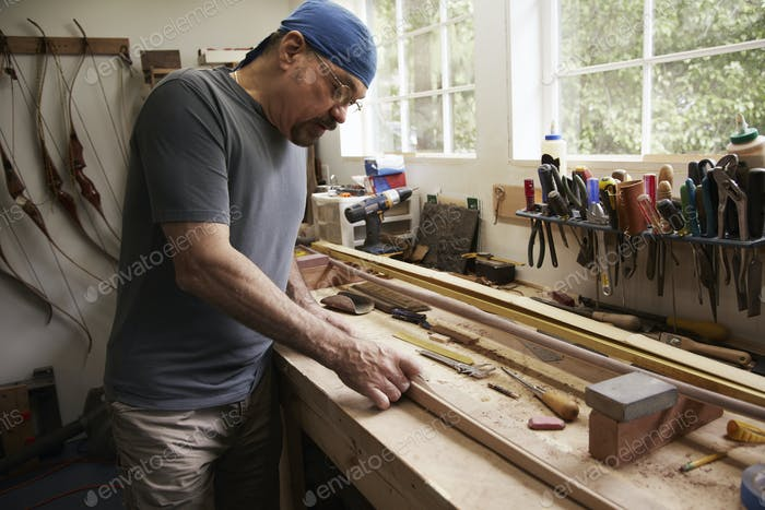 A bow maker working on a wooden bow in his workshop.