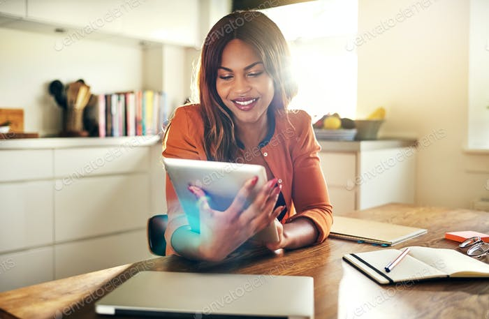 Young female entrepreneur using a digital tablet in her kitchen