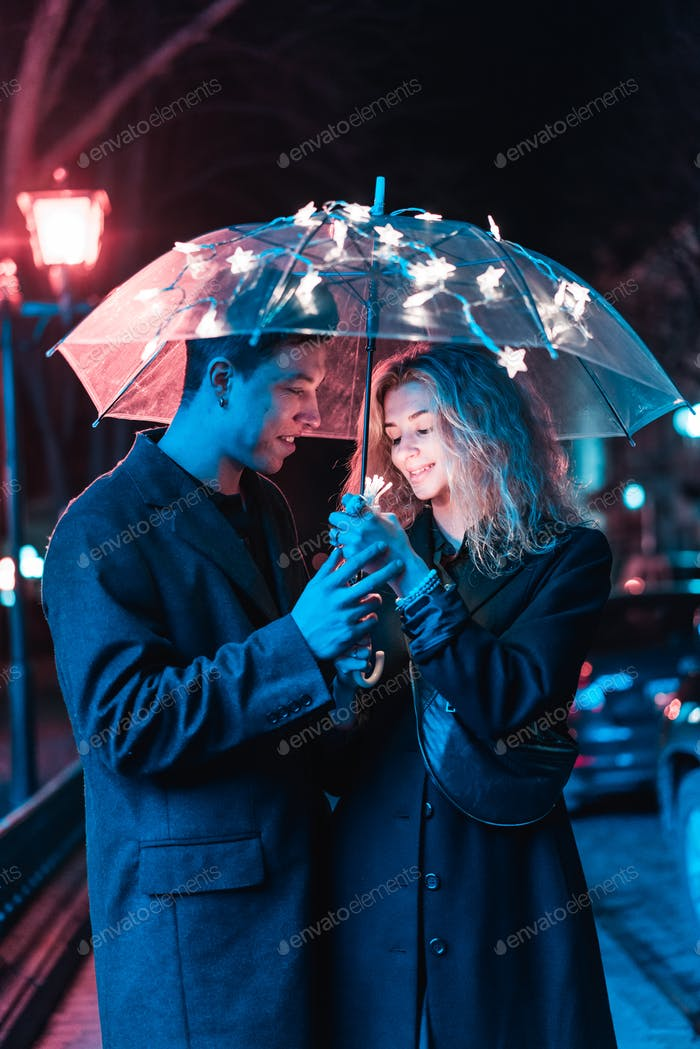 Portrait of a guy and a girl under an umbrella