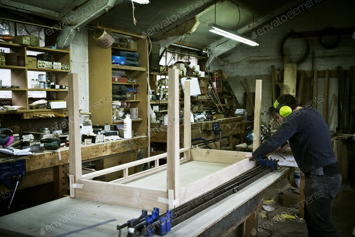A man working in a furniture maker's workshop, assembling a table.