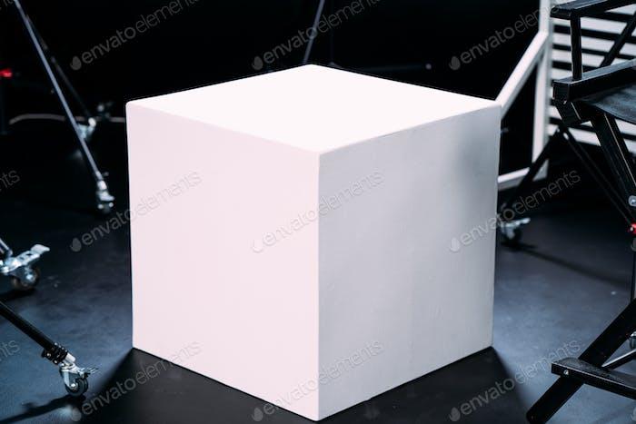 Modern photo studio with professional equipment. White cube on balck cyclorama
