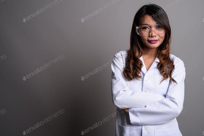 Asian woman doctor wearing protective glasses against gray backg