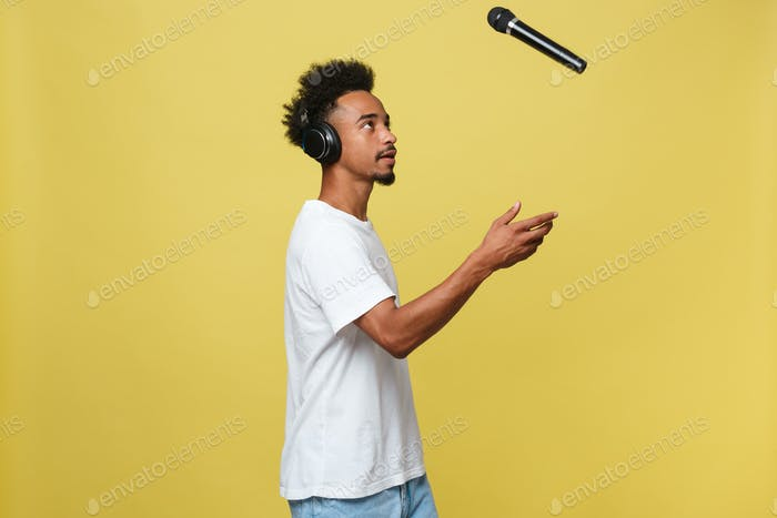 Handsome Black man throwing a microphone and singing. Isolated over a yellow background