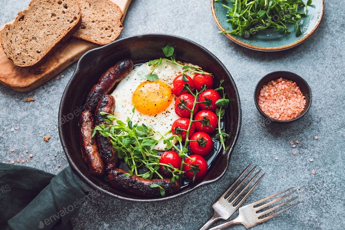 Breakfast time, fried egg with sausages and cherry tomatoes in a black iron pan, served microgreens.