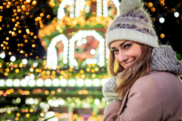 Beautiful woman in winter clothes on the background of Christmas decorations on a city street