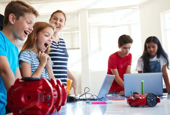 Excited Students Watching Robot Vehicle Move After Coding Lesson In Computer Programing Class