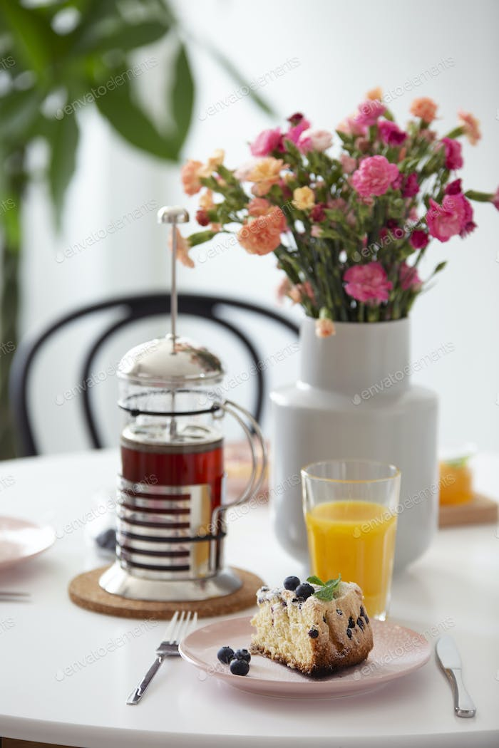 Flowers and orange juice on table with tea and dessert in a rest
