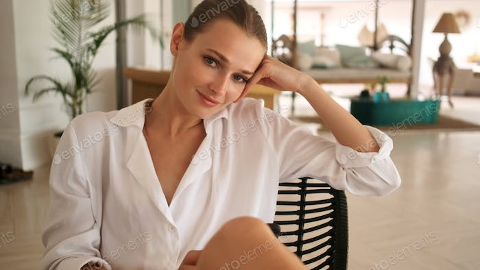 Gorgeous girl confidently looking in camera resting in living room of modern comfortable villa