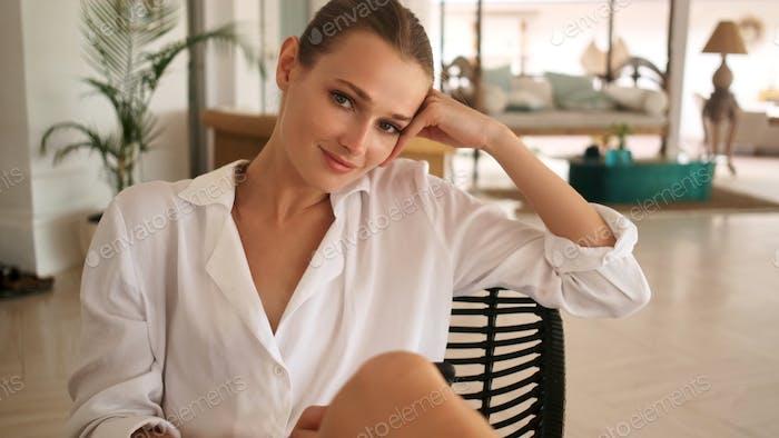 Великолепная девушка уверенно смотрит в камеру отдыхает в гостиной современной комфортной виллы