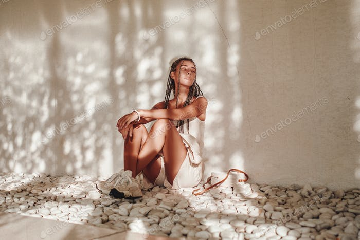 Woman in white summer clothing sitting leaning wall