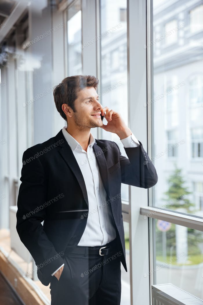 Happy young businessman talking on mobile phone in office