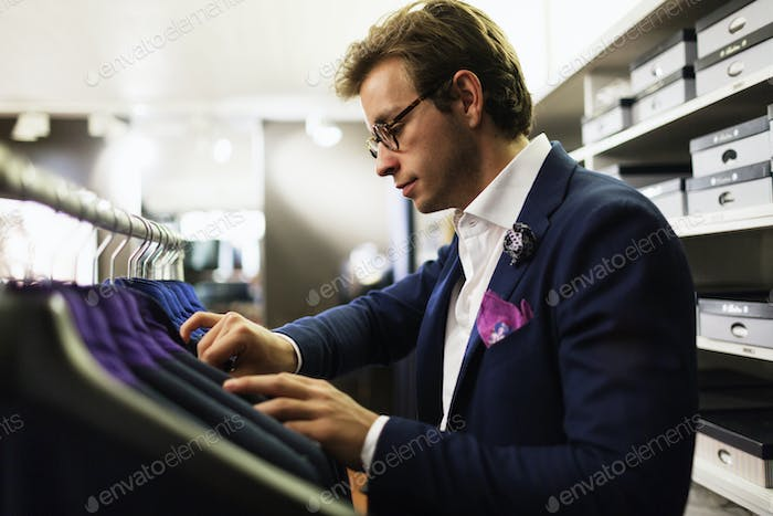 Salesman analyzing suits hanging on rack at clothing store
