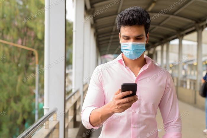 Young Indian businessman with mask using phone at the footbridge
