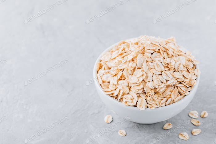 Bowl with raw oatmeal (oat flakes)