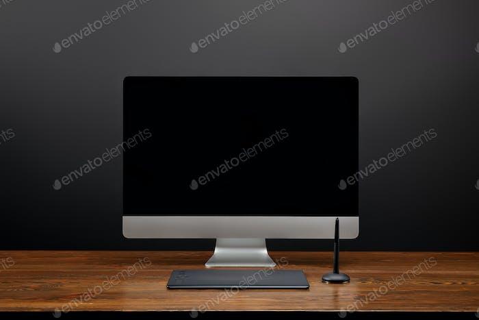 vista de cerca del lugar de trabajo del diseñador con pantalla de ordenador en blanco y tableta gráfica sobre mesa de madera