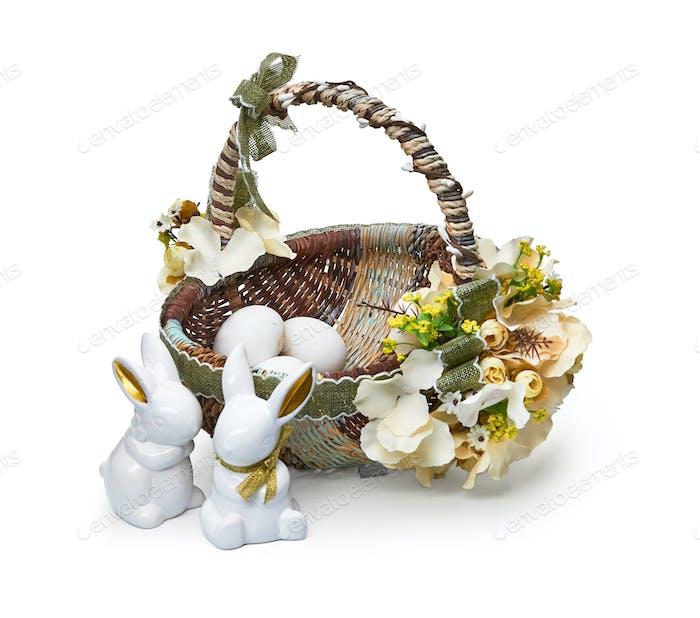 Osterkorb aus einem Blumenarrangement und einem Kaninchen auf weißem Hintergrund