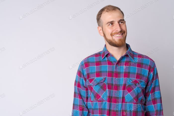 Portrait of happy young bearded hipster man thinking