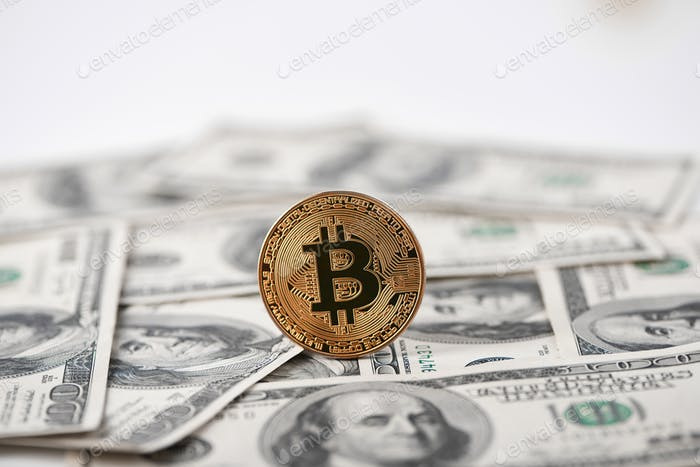 Golden bitcoin with hundred dollar banknotes on background