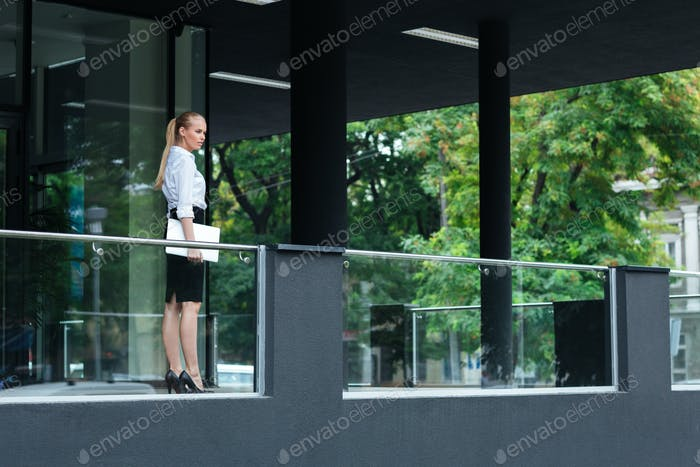 Young businesswoman holding laptop standing at the glass building