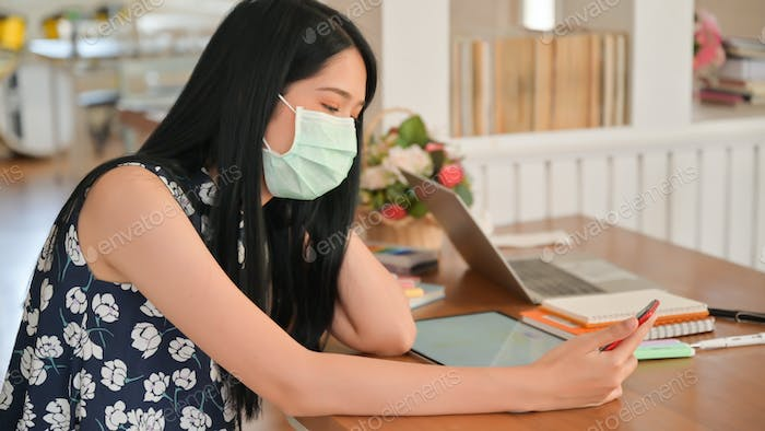 Woman wearing a mask is using smartphone in cafe.She is at risk of being infected with Covid-19.