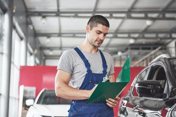 Porträt eines Mechanikers bei der Arbeit in seiner Garage - Autoservice, Reparatur, Wartung und Personenkonzept