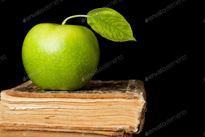 Green apple on book isolated