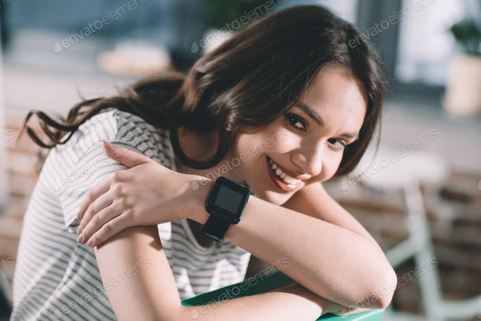 portrait of smiling woman with smartwatch on wrist