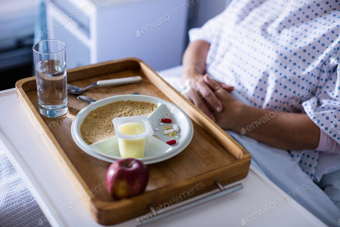Tray with apple and medicine kept on front of patient