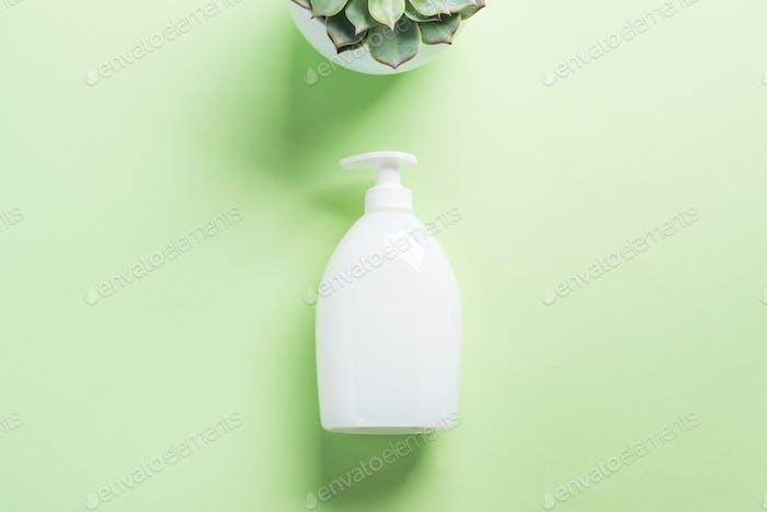 Weiße natürliche Seifenflasche auf Pastellgrün