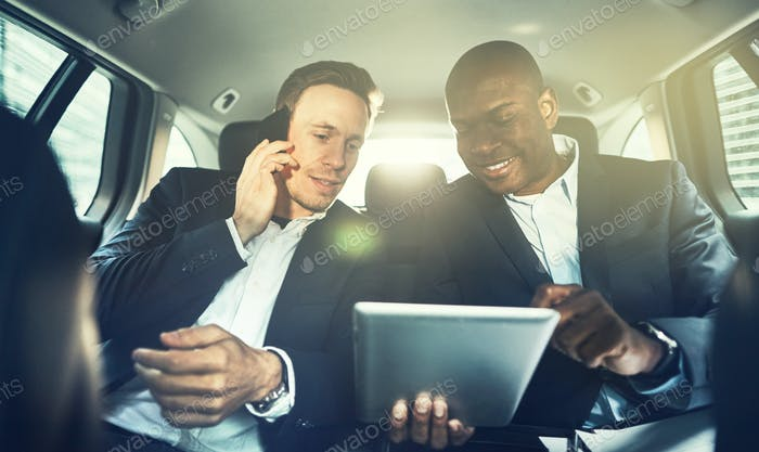 Two colleagues working together in the backseat of a car