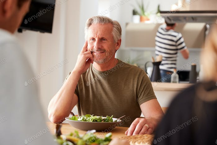 Family With Senior Parents And Adult Offspring Eating Meal Around Table At Home Together