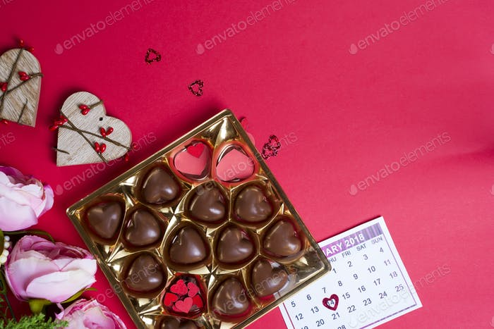 Delicious chocolate candies in gift box on red background