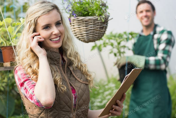 Smiling blonde woman phoning in a green house with boyfriend in background