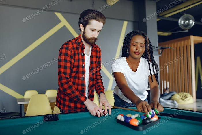 International couple playing a billiard in a club