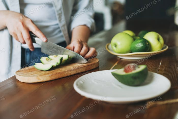 Female hands cut avocado on wooden working surface in kitchen at the home