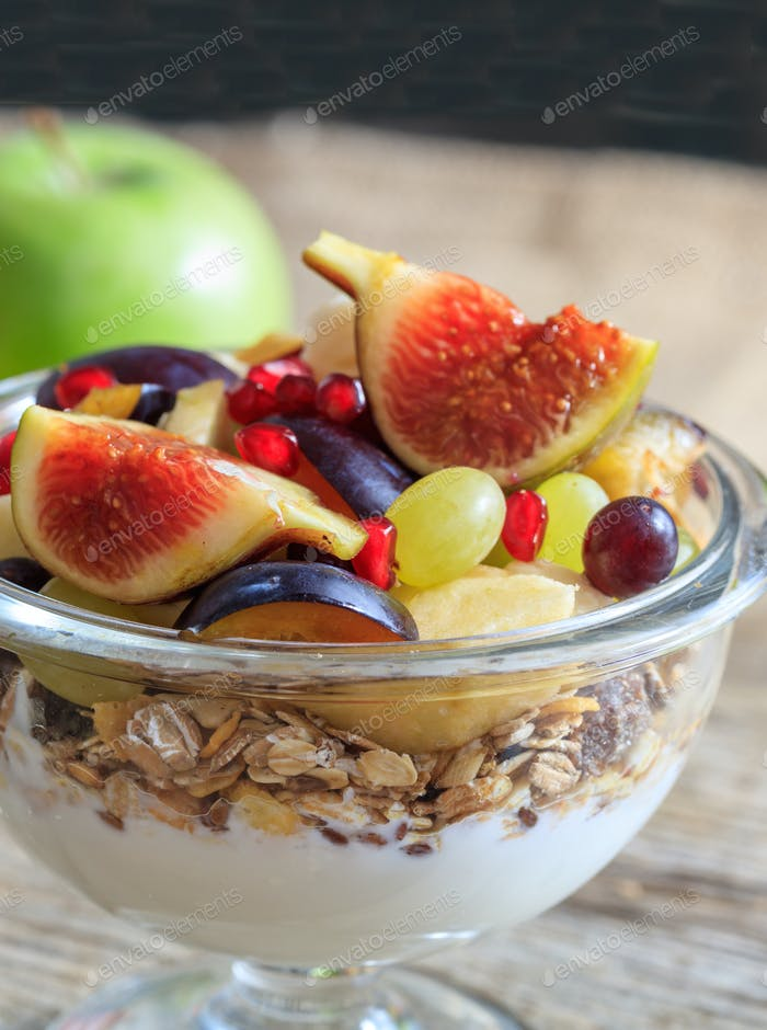Breakfast with Yogurt, muesli and fresh fruits in a bowl, blur background