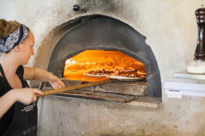 Weiblicher Koch Putting Pizza in Holzofen