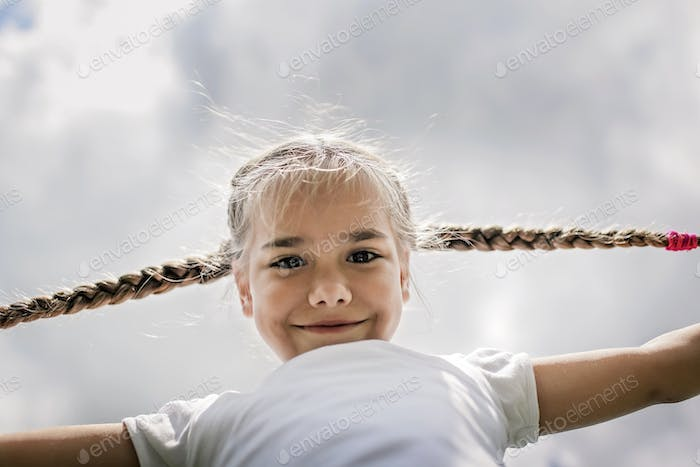 Close-up candid portrait of cute girl with two funny braids taken up at the sky from the ground