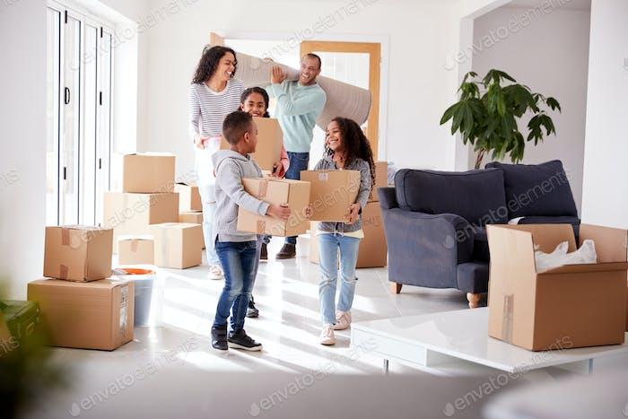 Lächelnde Familie tragen Boxen in neues Zuhause auf Umzug Tag